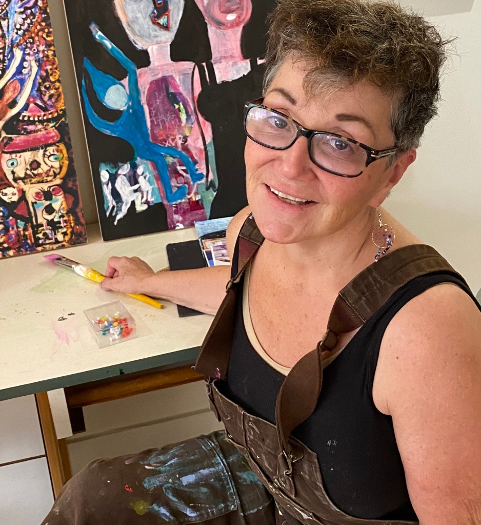 A woman artist wearing glasses with a smile having just turned to say hello to discover she is being photographed.